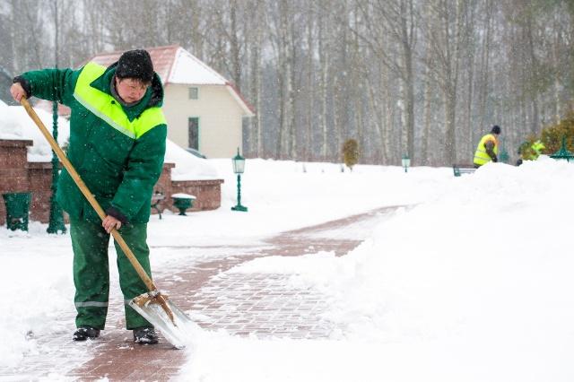 Дворник убирает снег лопатой