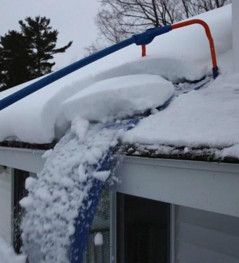 Уборка снега с крыши специальным скребком